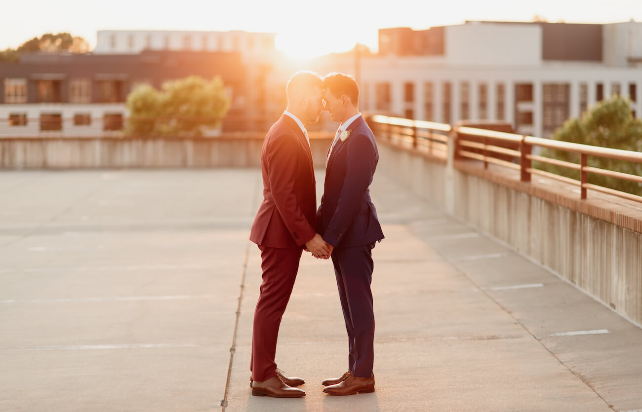 Two grooms on Durham rooftop at sunset